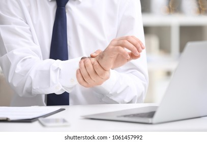 Young man suffering from wrist pain in office