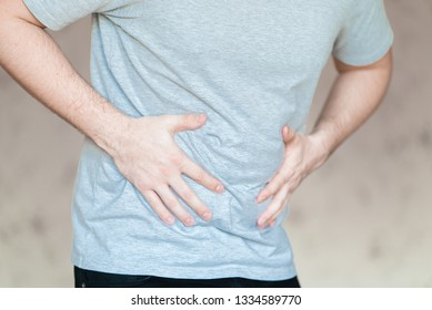 A young man suffers from abdominal pain and holds his hand on his stomach. Diarrhea or constipation in adults. The man has stress.