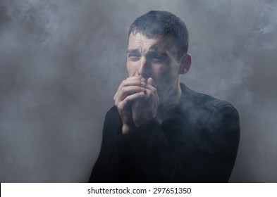 young man suffocating in the poisonous smoke