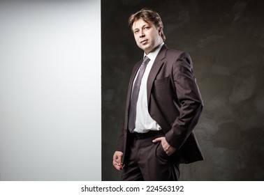 Young man in suit with banner for your text over grunge grey background