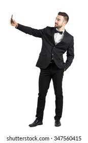 Young man in suit with bow tie taking selfie with cellphone. Full body length portrait isolated over white studio background.