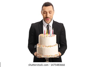 Young man in a suit holding a birthday cake and blowing candles isolated on white background