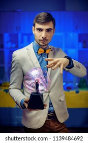 Young man in suit holding hand over plasma sphere in science lab.
