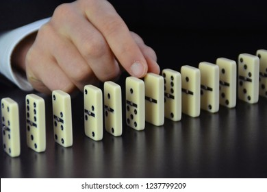 A young man in a suit and jacket removes a domino from a series of dominoes and prevents such a chain reaction when falling over - concept with a business man who intervenes before a catastrophe