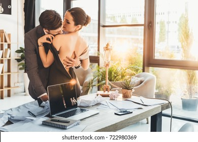 Young man in suit kissing beautiful woman in black dress on shoulder in his office