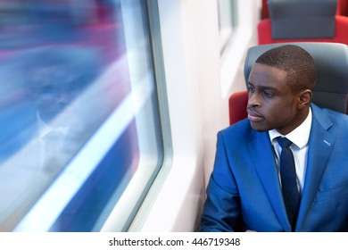 Young man in a suit on seat in train