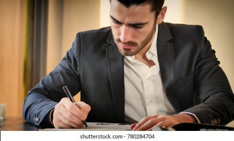 Young man in suit reading newspaper while sitting at table in office.