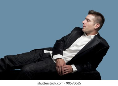 Young man  in suit relaxes on the bench at the studio