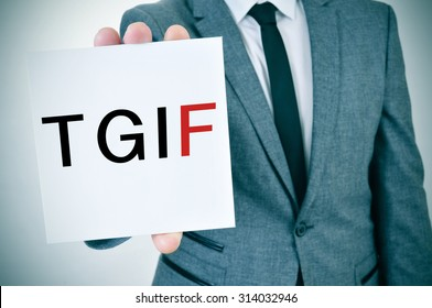 a young man in suit shows a signboard with the word TGIF, Thanks God It is Friday, written in it