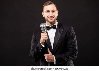 Young man in suit singing over the microphone with energy. Isolated on dark background. Singer concept.