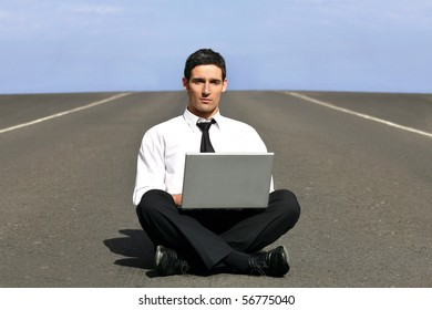 Young man in suit sitting in front of a laptop computer