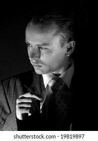 Young man in suit smoking cigarette side-view