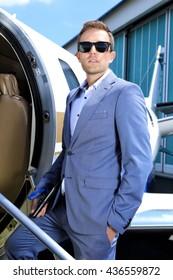 Young man in suit standing in the door of Business jet