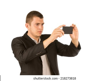 Young man in a suit taking a photo with his mobile phone concentrating as he composes and focuses the shot, isolated on white