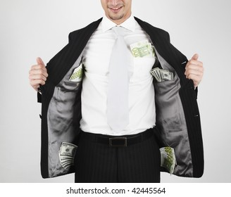 young man in suit that carry money (100s of dollar and euro) in his pockets.
