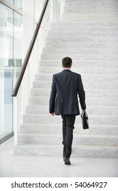 Young man with a suitcase climbing stairs