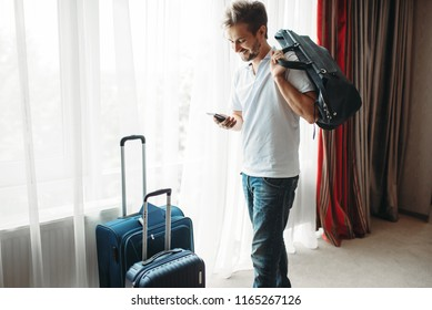 Young man with suitcases prepares for a journey