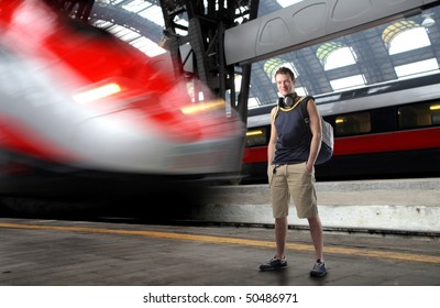 Young man in summer clothes standing on the platform of a train station