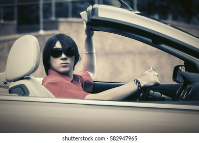 Young man in sunglasses driving convertible car Stylish fashion model outdoor