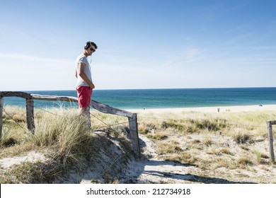 Young man with sunglasses and headphones standing on footpath on dune and listening music. He has his hands in pocket.