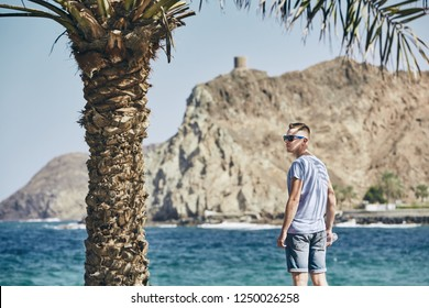 Young man with sunglasses in shadow of palm tree. Tourist on seashore in Muscat, Sultanate of Oman.