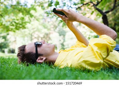 Young man with sunglasses texting on the grass