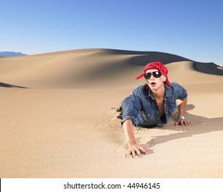 Young man in sunglasses wearing red bandana crawling in sand. Horizontal shot.
