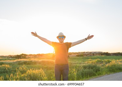 young man at sunset raises his hands up