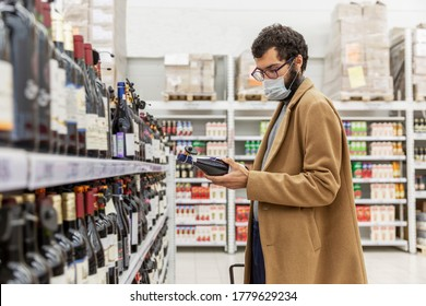 A young man in a supermarket chooses alcohol in the wine section. A brunette in a beige coat with a beard wearing a medical mask during the coronavirus pandemic.