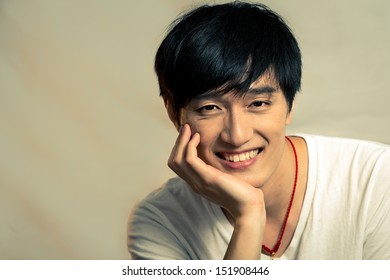 Young man supporting chin and smiling, with fashion tone