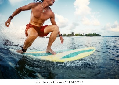 Young man surfer rides the ocean tropical wave during sunrise surf session