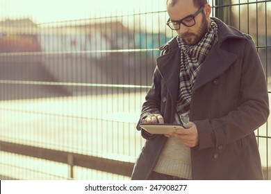 Young man surfing the internet on a tablet outdoor