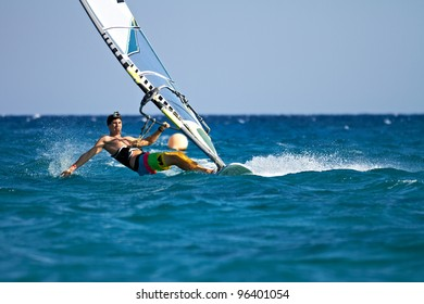Young man surfing the wind and touching water surface with splashes