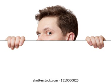 Young man with surprised eyes peeking out from behind billboard paper poster. Funny man peeking from behind the desk isolated on white background with copy space