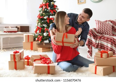 Young man surprising his girlfriend with Christmas gift at home