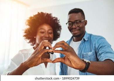Young man surprising his wife or a girl with new a apartment. Young smiling African-American couple showing keys to new home hugging looking at camera.