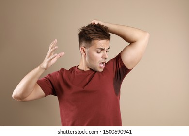 Young man with sweat stain on his clothes against beige background. Using deodorant