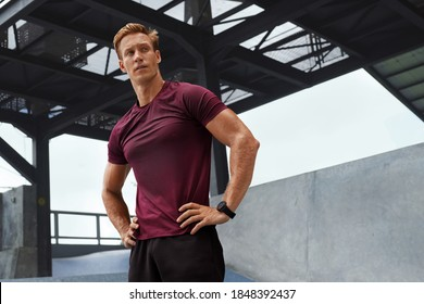 Young Man In Sweaty Shirt Resting After Intense Workout Against Concrete Wall. Handsome Caucasian Sportsman With Strong Muscular Body In Fashion Sportswear Looks Tired And Exhausted.