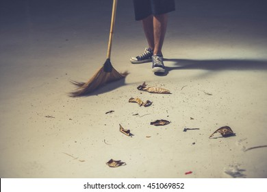 Young man sweeping dried leafs on the floor with local nature broom