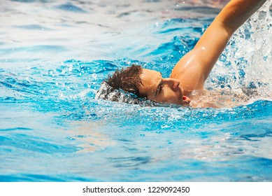 Young man swimmer train swimming in swimming pool. Recreation outdoor water sport.