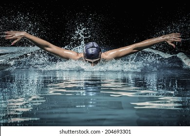 Young man in swimming cap and goggles swim using breaststroke technique