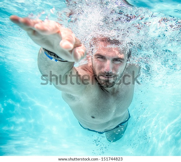 Young man swimming the front crawl in a pool, taken underwater