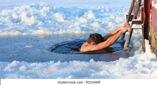 Young man swimming in an ice hole