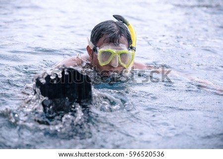 742bc5c0aeea Young man swimming underwater in the pool wearing snorkel and scuba shoes (drive  slippers