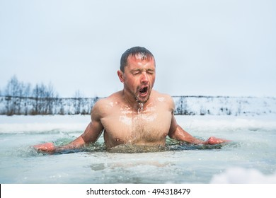Young man swimming in the winter lake in the ice hole