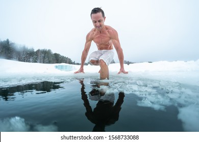 Young man swims in the ice hole made on the winter lake