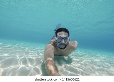 Young man swims in the sea - Millennial does snorkeling in the ocean in the summer