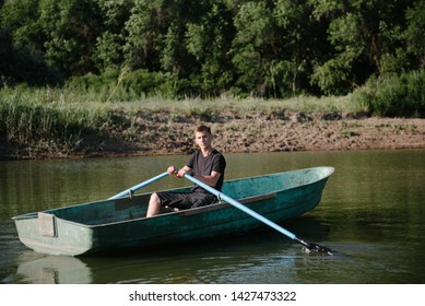 A young man swims in a small wooden boat with oars on the river