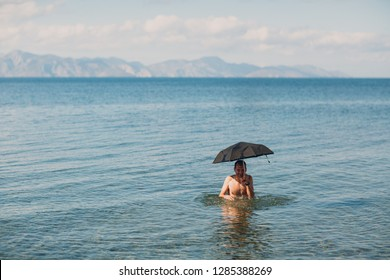 Young man swims with an umbrella in the sea