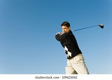 Young man swinging golf club against clear sky